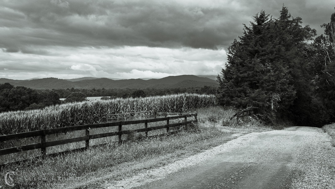 20180822_006_BW: clouds, fence, summer, Blue Ridge Mountains, gravel road, corn field