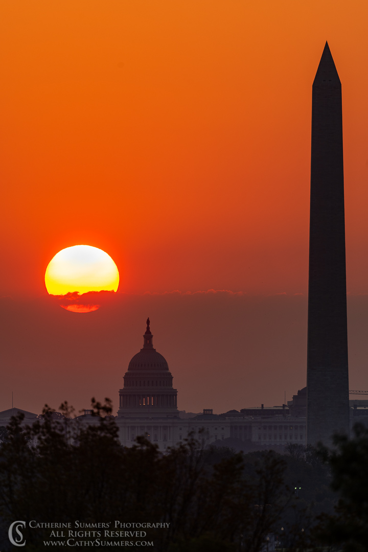 Sun Rising Through Clouds Over the US Capitol and Washington Monument